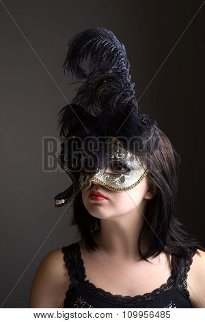 young teenager girl wearing black venetian mask with feathers on a dark grey background