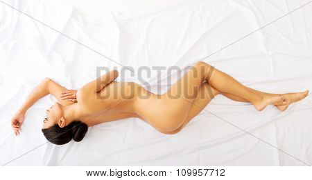 Spa nude woman lying down on a bedsheet.