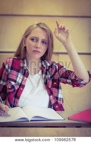 Unsure student raising the hand during class at the university