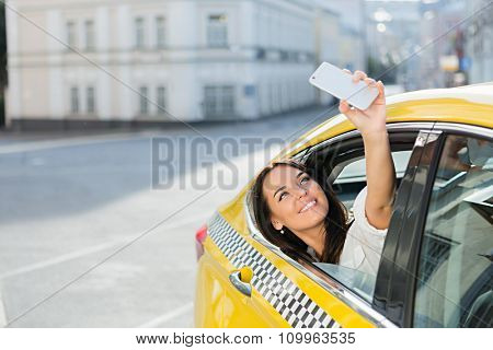 Young girl makes selfie in a taxi