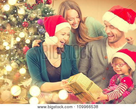 Christmas Family - Father, Mother and children opening Christmas gifts over Decorated Christmas tree. Happy Smiling Parents and Kids at Home Celebrating New Year. Christmas Tree. Christmas scene