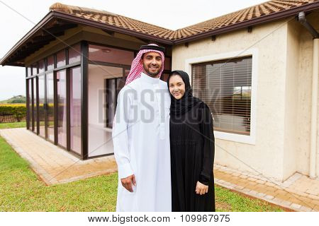 portrait of lovely young muslim couple standing in front of their house