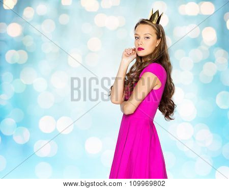 people, holidays and fashion concept - young woman or teen girl in pink dress and princess crown over blue holidays lights background