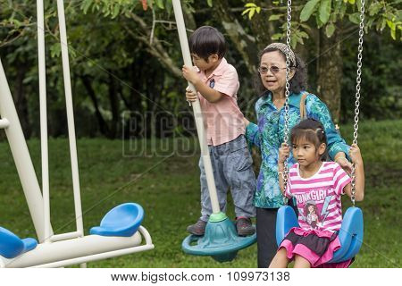 Asian Family On A Swing In Park