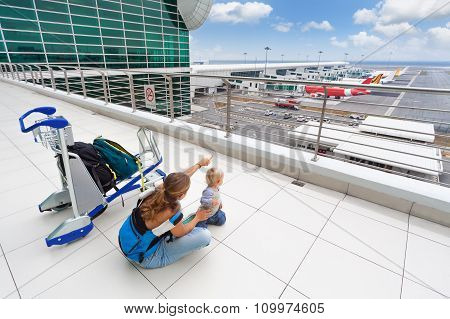 Young Mother Show To Baby Boy Airplanes In Airport