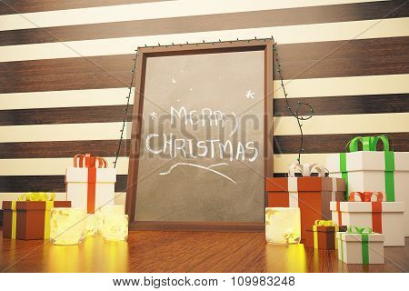 Picture Frame With Merry Christmas Lettering And Gift Boxes On Wooden Floor