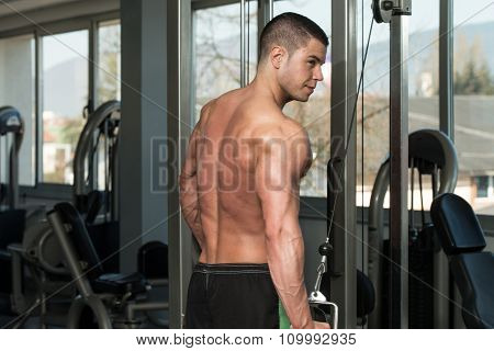 Young Bodybuilder Is Working On His Triceps With Cable In A Dark Gym poster