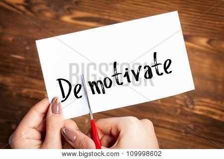 Woman hands cutting card with the word demotivate