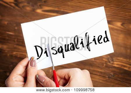 Woman hands cutting card with the word disqualified