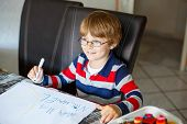 Portrait of cute happy preschool kid boy with glasses at home making homework. Little child writing mama with colorful pencils, indoors. School, education concept poster