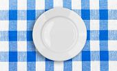 white plate on blue checked fabric tablecloth poster