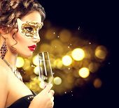 Sexy model woman with glass of champagne wearing venetian masquerade mask at party, drinking champagne over holiday glowing background. Christmas and New Year celebration poster