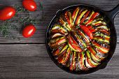 Vegetable ratatouille baked in cast iron frying pan homemade preparation recipe healthy diet french vegetarian food on vintage wooden table background. Top view. Rustic style. poster