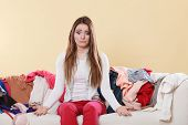 Helpless woman sitting on sofa couch in messy living room shrugging. Young girl surrounded by many stack of clothes. Disorder and mess at home. poster