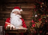 Santa Claus in wooden home interior sitting behind table and writing letters with quill pen poster