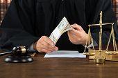 Midsection of male corrupt judge holding dollar bundle at desk in courtroom poster