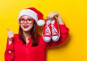 Portrait of a young redhead woman in Santa Claus hat and with gumshoes on yellow background poster