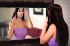 Attractive Woman Fixing Her Hairstyle Before The Big Mirror