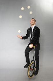 Smiling Man Juggles Balls