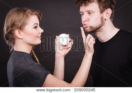 Hygiene and skincare concept. Young blonde female beautician cosmetician apply cream on male mouth lips. Woman and man playing with cosmetic.