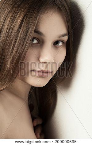 sensual girl near wall looking at camera, smiling
