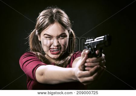 fun girl with gun on black background aiming at camera, show tongue
