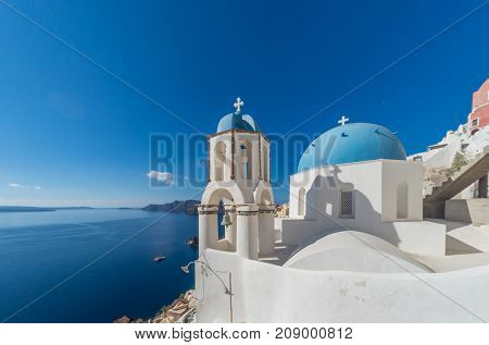 view of caldera with classical blue church domes, Oia, Santorini