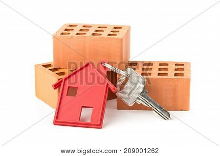 House door key with red house key chain pendant and bricks over white background