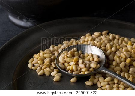Heap of raw uncooked pine nuts in metal spoon on rustic plate over dark kitchen background