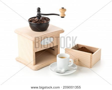 Coffee grinder with ground coffee coffee beans and cup of espresso on white background