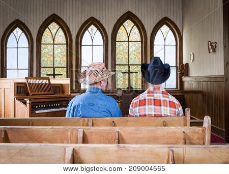horizontal image of two caucasian cowboys sitting in an old romantic church pew in front of a wall of arched windows and an old organ sitting beside them.