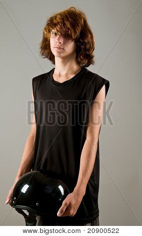 teen boy holding motorcycle helmet