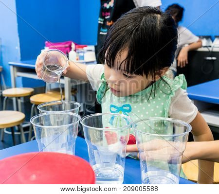 Kindergarten Girl Pouring Clear Solution Into A Cup On Blue Table.