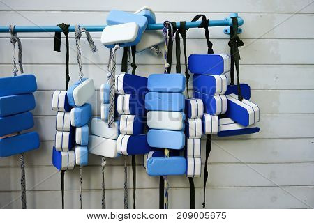 A Row Of Swimming Belts Hanging On Pvc Bar By Swimming Pool Against White Pattern Wall.