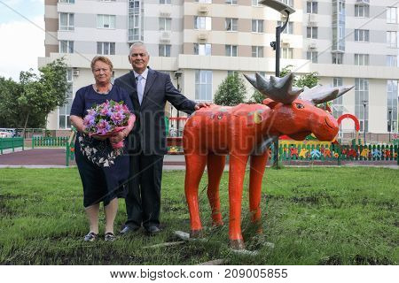 portrait of family elderly couple, man and woman with wooden sculpture of elk in courtyard of multi-storey building