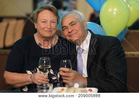 portrait of family elderly couple, man and woman on holiday holding glasses of wine, feast, smiling