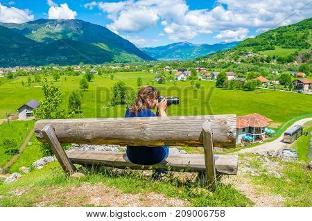 A Young Girl Takes Pictures On A Wooden Bench Near The Sources Of Ali Pasha.