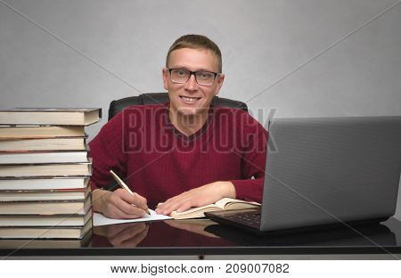 Young happy student man doing homework at the desk table. Young smiling business man signing contract or working with documents.