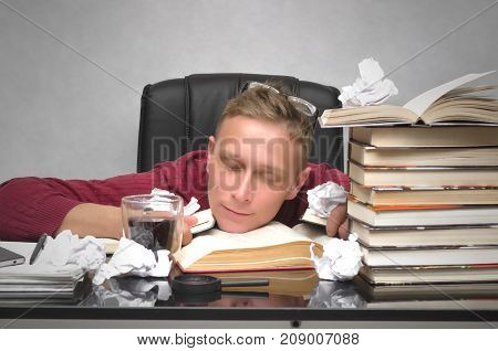 Student man tired of studying and sleeping on the school desk table with books and crumpled paper pages around. Tired employee worker. Overworked businessman. Hard job.