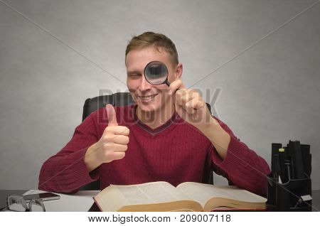 Find and search. Happy smiling business man looks through a magnifying glass and shows thumbs up sign by his hand. Education. Successful business man. Man's eye through a magnifying glass.