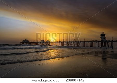Local wildfires pipeline golden brown smoke over the skies of Huntington Beach pier, creating a surreal sunset.