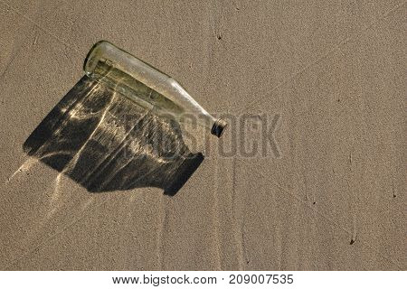 Glass bottle with shade from the sun on the beach.