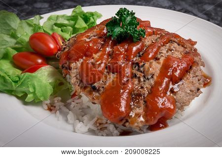 Hamburger meat with rice and salad on white plate