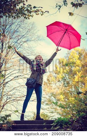 Autumn weather concept. Woman walking in park holding red umbrella fighting with strong wind