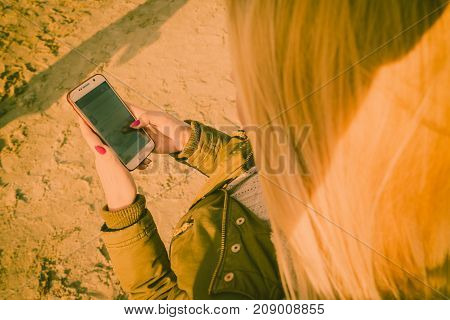 Social media technology modern devices internet concept. Woman teenager wearing warm coat using her smartphone while walking outside on beach