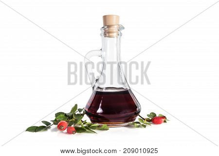 Syrup from a dogrose in a decanter rosehips green leaves isolated on a white background