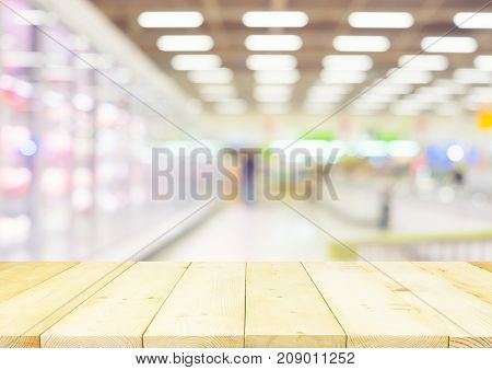 Blurred photo of fresh food in supermarket or shopping mall montage with wood table for background.