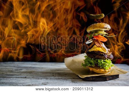 Hamburger with realistic flying ingredients. Tasty smoked grilled and glazed beef burger with lettuce, cheese and bacon on wooden table with copyspace. Open fire red flames in background.