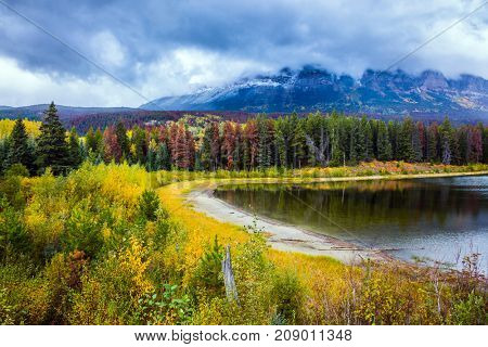 Multicolored autumn forests grow along the banks of the cold lake. Heavy storm clouds over the Rocky Mountains of Canada. The concept of active tourism