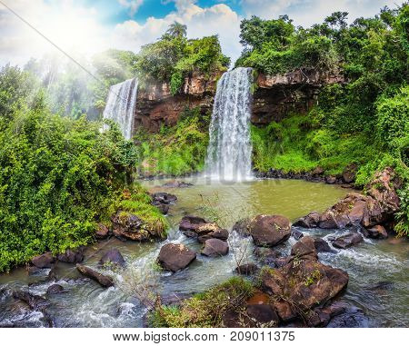 Hot tropical sun illuminates the rumbling waterfalls. Two rapid waterfalls from the Iguazu Falls in Argentina. The concept of extreme and ecological tourism